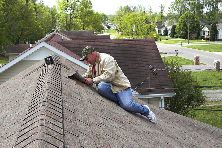 old man on the roof installing new roof tiles